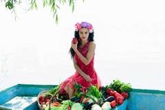 Donna sulla barca con le verdure che tengono pepe Fotografia Stock