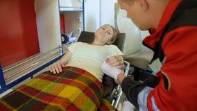 Donna sulla barella che tiene la mano di medico, ambulanza che trasporta paziente alla clinica archivi video