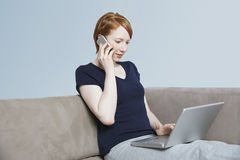 Donna sulla chiamata mentre per mezzo del computer portatile Immagine Stock