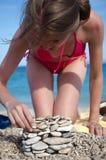 Donna sulla costruzione di edifici della spiaggia dei ciottoli Fotografie Stock