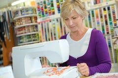 Donna sulla macchina per cucire Immagini Stock Libere da Diritti