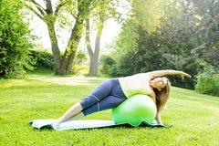Donna sulla palla dell'equilibrio di yoga Immagini Stock Libere da Diritti