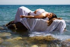 Donna sulla pietra e sul mare Fotografia Stock