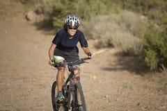 Donna sulla scalata della bici Fotografie Stock Libere da Diritti