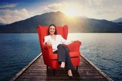 Donna sulla sedia rossa sull'ormeggio Fotografia Stock Libera da Diritti
