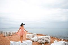 Donna sulla spiaggia abbandonata con molti lettini Fotografie Stock