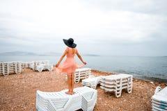 Donna sulla spiaggia abbandonata con molti lettini Immagini Stock Libere da Diritti