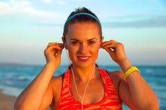 Donna sulla spiaggia al tramonto con le cuffie che ascolta la musica Fotografie Stock