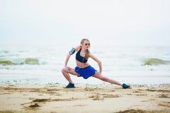 Donna sulla spiaggia che fa allungando esercizio dopo un allenamento Immagine Stock
