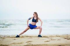 Donna sulla spiaggia che fa allungando esercizio dopo un allenamento Fotografie Stock