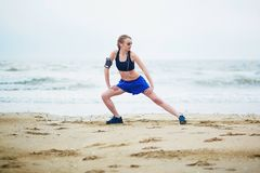 Donna sulla spiaggia che fa allungando esercizio dopo un allenamento Fotografia Stock Libera da Diritti