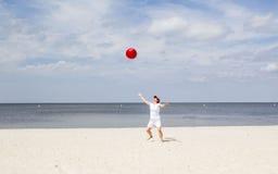 Donna sulla spiaggia che getta un beach ball rosso nell'aria Fotografie Stock Libere da Diritti