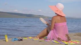 Donna sulla spiaggia che legge un libro video d archivio
