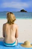 Donna sulla spiaggia che prende il sole Immagine Stock
