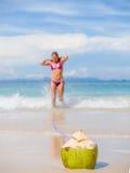 Donna sulla spiaggia con la bevanda della noce di cocco Fotografie Stock