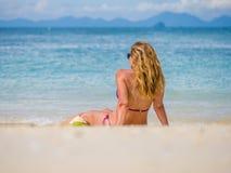 Donna sulla spiaggia con la bevanda della noce di cocco Immagini Stock
