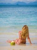 Donna sulla spiaggia con la bevanda della noce di cocco Fotografia Stock Libera da Diritti