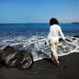 Donna sulla spiaggia nera della sabbia fotografia stock libera da diritti