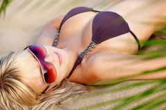 Donna sulla spiaggia, ponente sotto il sole Immagini Stock
