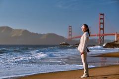 Donna sulla spiaggia vicino a golden gate bridge immagini stock