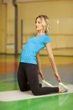 Donna sulla stuoia nella classe di forma fisica Allungamento femminile dopo l'allenamento Fotografie Stock