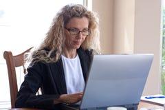 Donna sulla tabella con il computer portatile Fotografie Stock Libere da Diritti