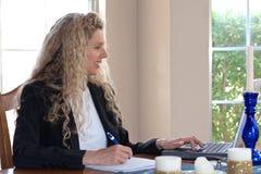 Donna sulla tabella con il computer portatile Immagini Stock