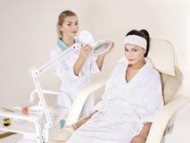 Donna sulla tabella di massaggio nella stazione termale di bellezza. Immagine Stock