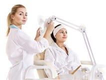 Donna sulla tabella di massaggio nella stazione termale di bellezza. Fotografia Stock