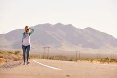 Donna sulla vacanza che fa auto-stop lungo la strada facendo uso del telefono cellulare Fotografia Stock Libera da Diritti