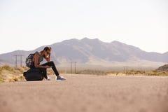 Donna sulla vacanza che fa auto-stop lungo la strada facendo uso del telefono cellulare Fotografie Stock Libere da Diritti
