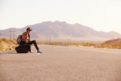 Donna sulla vacanza che fa auto-stop lungo la strada facendo uso del telefono cellulare Fotografie Stock