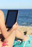 Donna sulle vacanze che legge una compressa sulla spiaggia immagine stock