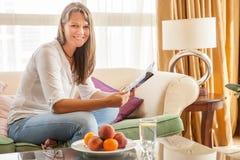 Donna sullo strato con una rivista immagini stock libere da diritti