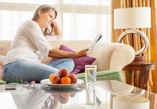 Donna sullo strato con una rivista Immagine Stock