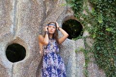 Donna in sundress alla parete di pietra Immagine Stock