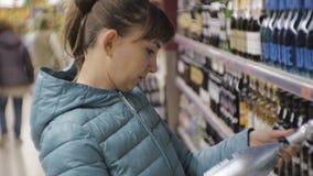 Donna in supermercato Giovane donna caucasica in giacca blu che legge l'etichetta sulla bottiglia che sceglie vino spumante archivi video