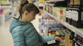 Donna in supermercato Giovane donna caucasica in giacca blu che legge l'etichetta sulla bottiglia scura che sceglie vino rosso stock footage