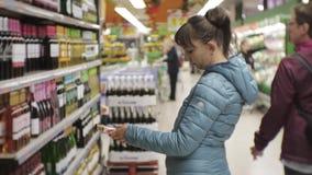 Donna in supermercato Giovane donna caucasica in giacca blu che legge l'etichetta sulla chiara scelta della bottiglia bianca video d archivio