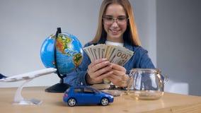 Donna sveglia bella che prende soldi dal barattolo di vetro sulla tavola con il globo, l'automobile del giocattolo e l'aereo archivi video
