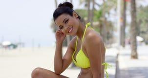 Donna sveglia in bikini giallo che si siede sulla parete della spiaggia stock footage