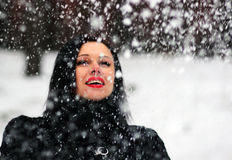Donna sveglia che gioca con la neve in pelliccia all'aperto immagini stock
