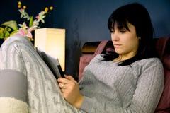 Donna sveglia che si siede a letto rilassamento guardando rete sociale sulla compressa immagini stock