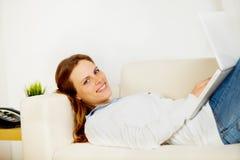 Donna sveglia che sorride e che si trova sul sofà Fotografia Stock