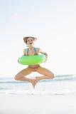 Donna sveglia che tiene un anello di gomma mentre saltando sulla spiaggia Immagini Stock