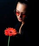 Donna sveglia che tiene un fiore rosso Immagine Stock