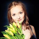 Donna sveglia con i fiori della primavera fotografia stock libera da diritti