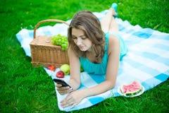 Donna sveglia con il canestro di picnic e frutti che si trovano e che usando p astuta Immagine Stock