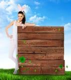 Donna sveglia con le orecchie del coniglietto con un segno in bianco di legno Fotografia Stock