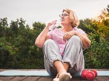 Donna sveglia e adulta che fa esercizio nel parco su un fondo di cielo blu ed in alberi verdi un chiaro, giorno soleggiato Concet immagine stock